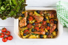 Baked chicken drumsticks in red dish. Cooked with cherry tomatoes, black olives, rosemary and potatoes. White wooden table, top view Royalty Free Stock Photos