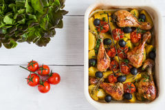 Baked chicken drumsticks in red dish. Cooked with cherry tomatoes, black olives, rosemary and potatoes. White wooden table Royalty Free Stock Image