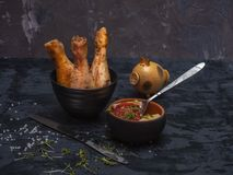 Baked chicken drumsticks, vegetable and egg salad, black crockery and cutlery stock photo