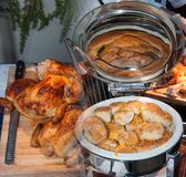 Baked chicken and fancy rolls. Baked chickens to the left and fancy bowl of rolls to the right, images blended together royalty free stock photo