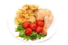 Baked chicken leg with potatoes and tomatoes Royalty Free Stock Images