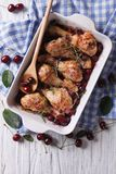 Baked chicken legs in cherry sauce in a dish vertical top view Stock Photo