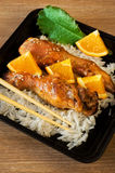 Baked chicken legs with rice and orange Stock Images