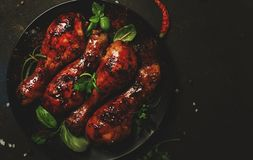 Baked chicken legs in spicy glaze with honey sauce on the plate, black kitchen table background, asian food, top view stock photos