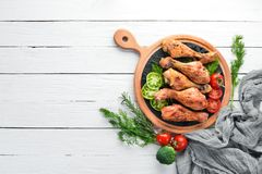 Baked Chicken legs on a white wooden background. Meat. Top view. Free copy space royalty free stock images