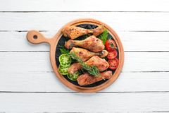Baked Chicken legs on a white wooden background. Meat. Top view. Free copy space stock photos