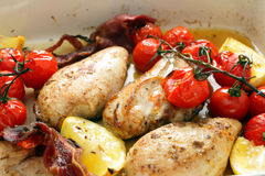 Baked chicken lemon and tomatoes Stock Images