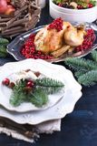 Baked chicken on a platter with red berries. on a blue wooden table with a bowl, serving plates. stock image