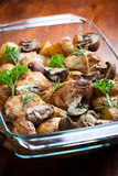 Baked chicken on potatoes and mushrooms Stock Photos