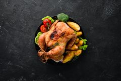 Baked chicken with potatoes and vegetables on a black background. The traditional dish for Thanksgiving. Top view. Free copy space royalty free stock photography