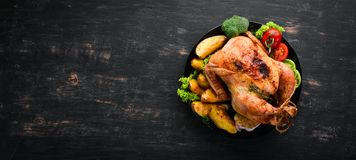 Baked chicken with potatoes and vegetables on a black background. The traditional dish for Thanksgiving. Top view. Free copy space stock photos