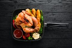 Baked chicken with potatoes and vegetables on a black background. The traditional dish for Thanksgiving. Top view. Free copy space royalty free stock images