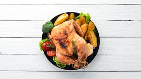 Baked chicken with potatoes and vegetables on a white wooden background. The traditional dish for Thanksgiving. Top view. Free copy space royalty free stock photo
