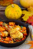 The baked chicken with pumpkin in a pig-iron frying pan Royalty Free Stock Images