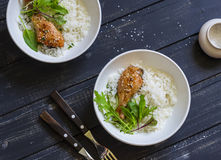 Baked chicken, rice and salad in a bowl on a dark wooden background. royalty free stock photo