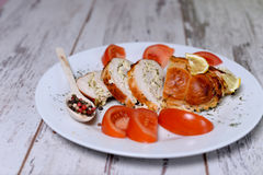 Baked chicken rolls with tomato and lemon and spices on white plate on a white wooden table. Baked chicken rolls with tomato and lemon and spices on a white Royalty Free Stock Images