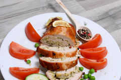 Baked chicken rolls with tomato and lemon and spices on white plate on a white wooden table. Baked chicken rolls with tomato and lemon and spices on a white Stock Photo