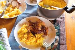 Baked chicken, saffron rice and pot with rice on table. Baked chicken with saffron rice, two portion on plate, rice in pot on table Royalty Free Stock Images