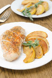 Baked chicken and saute quince with rosemary vertical Stock Photo