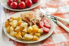 Baked chicken thigh with baked potatoes and pumpkin garnish on a. Plate royalty free stock images