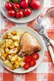 Baked chicken thigh with baked potatoes and pumpkin garnish on a. Plate stock photos
