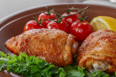 Baked chicken thigh. With cherry tomatoes and lemon royalty free stock photography