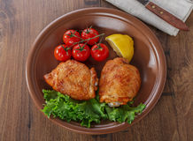 Baked chicken thigh. With cherry tomatoes and lemon royalty free stock photo