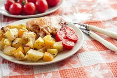 Baked chicken thigh with baked potatoes and pumpkin garnish. On a plate royalty free stock photo