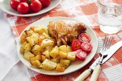 Baked chicken thigh with baked potatoes and pumpkin garnish. On a plate stock image