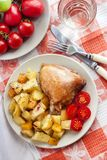 Baked chicken thigh with baked potatoes and pumpkin garnish. On a plate royalty free stock images