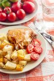 Baked chicken thigh with baked potatoes and pumpkin garnish on a. Plate stock images