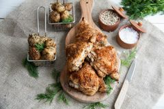 Baked chicken thighs lying on a wooden board with greens and baby potato. Lunch or dinner idea: Baked chicken thighs lying on a wooden board with greens and baby royalty free stock image