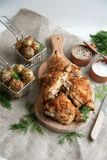 Baked chicken thighs lying on a wooden board with greens and baby potato. Lunch or dinner idea: Baked chicken thighs lying on a wooden board with greens and baby stock photos