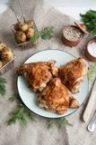 Baked chicken thighs lying on a wooden board with greens and baby potato. Lunch or dinner idea: Baked chicken thighs lying on a wooden board with greens and baby stock images