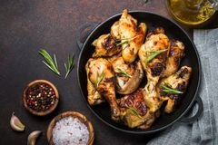 Baked chicken top view. Chicken baked in iron pan on dark stone table. Top view with copy space royalty free stock photo