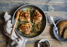 Baked chicken in white wine in the pan. On rustic wooden background royalty free stock photos