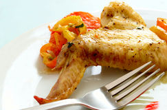 Baked chicken wing on a plate and fork Stock Photography