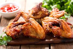 Baked chicken wings. On wooden table stock photo