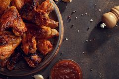Baked chicken wings with bbq sauce on the plate on rusty background. Top view with free space royalty free stock images