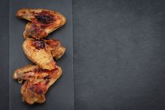 Baked chicken wings on dark background with copy space. Top view royalty free stock images