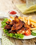 Baked chicken wings with French fries on wooden table. royalty free stock photography