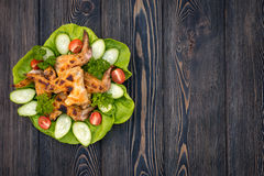 Baked chicken wings with green salad leaves on a wooden table , close-up view.View from above. Space for text . royalty free stock photo