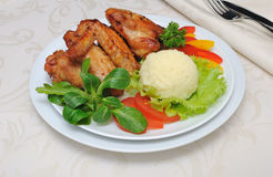 Baked chicken wings with garlic and potatoes and vegetables Royalty Free Stock Photography