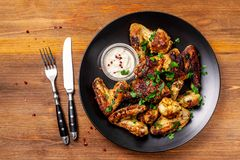 Baked chicken wings in Mexican with curry seasoning and parsley on a black plate, on a wooden background. side view, copy space. Top view stock image