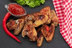 Baked chicken wings with sesame and sauce. Food background. Top view royalty free stock images
