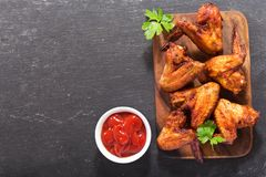 Baked chicken wings on wooden board. Top view Stock Images