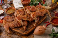 Baked chickens on a wooden board with sauces of different types in ceramic cups. royalty free stock photo