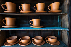 Baked clay coffee cup on wooden shelf Royalty Free Stock Photo
