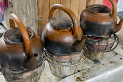 Baked clay kettle with hot water on stove. Stock Images
