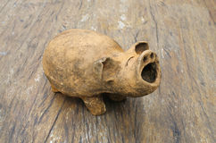 Baked-clay pig on wood table Stock Photo